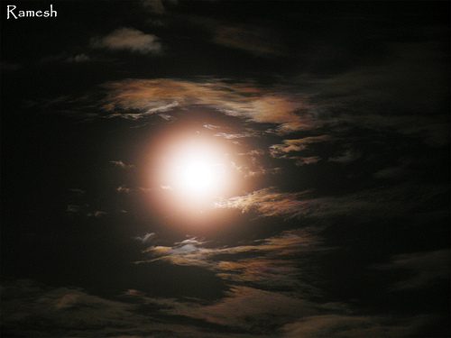 a full moon shining through the clouds
