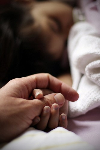Holding a child's hand as they sleep